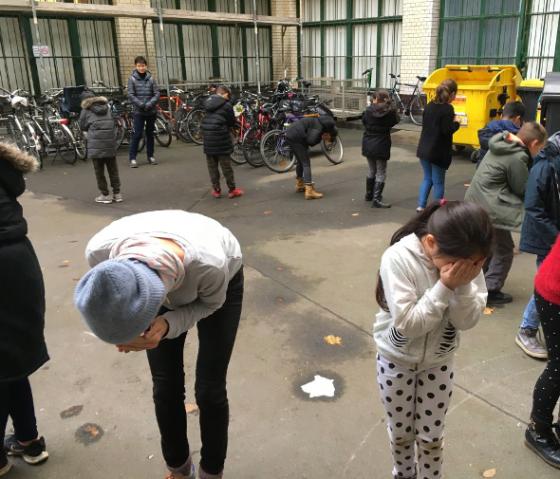 Veranstaltungsfoto einer Gruppe von Kindern im Kreis im Hof des Museums, sie drehen sich den Rücken zu und verdecken die Augen