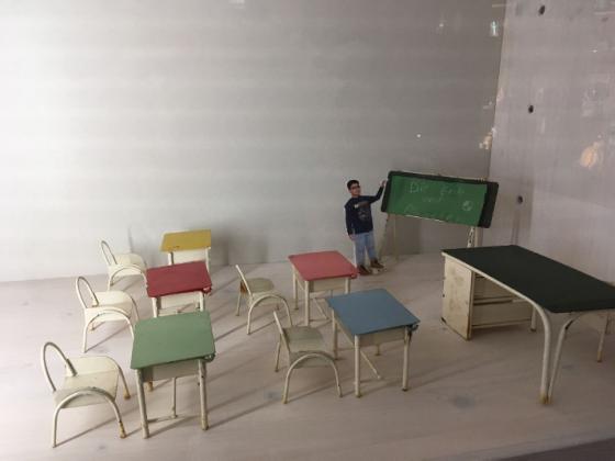 Veranstaltungsfoto Einsicht in eine Vitrine mit einem Miniatur-Klassenzimmer, an einer kleinen Tafel ein Junge aus Papier