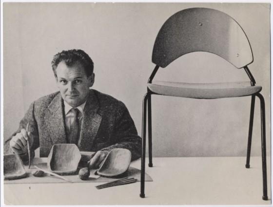 Schwarz-weiß-Foto von Herbert Hirche, sitzend vor kleinen Stuhl-Modell-Teilen und neben einem Stuhl, der auf einem Tisch steht
