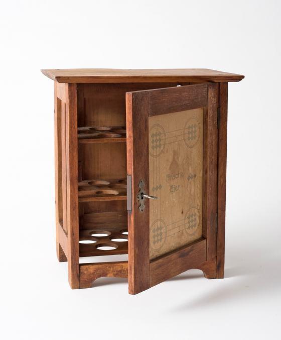 Geöffnetes Holzschränkchen mit drei Fächern mit runden Aussparungen und verzierter Tür